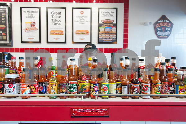 12/11/17 Wesley Bunnell | Staff Firehouse Subs opened for business on Monday at their new location at 594 Farmington Ave. Jason Lombardi stands behind bottles of hot sauce.