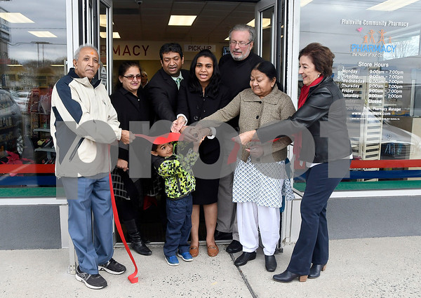 12/1/2017 Mike Orazzi | Staff Members of the Patel family cut the ribbon in front of the Plainville Community Pharmacy Friday afternoon during the grand opening.