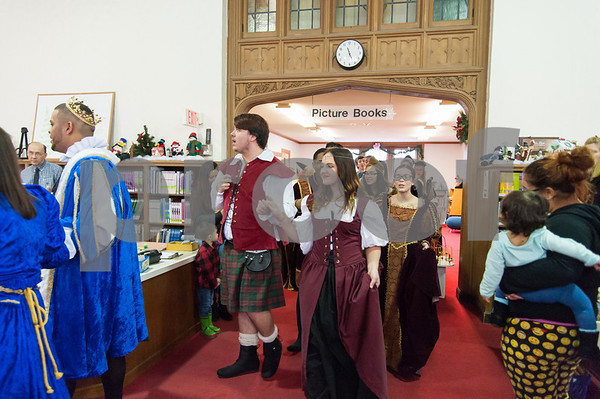 12/12/17 Wesley Bunnell | Staff The New Britain High School Madrigal Singers performed as they walked through the public library on Tuesday morning. Robert Breau, L, and Maeve Maltese exit the childrens section with the group.