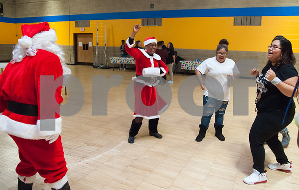 12/12/17 Wesley Bunnell | Staff New Britain OIC held their annual Christmas Party on Tuesday afternoon featuring food, music and presents for all members. Executive Director of the New Britain Downtown District Gerry Amodio, L, dances as Santa next to OIC Executive Director Paulette Fox dressed as Mrs. Claus and students Jasiry Valentin and Ashia Bravo.