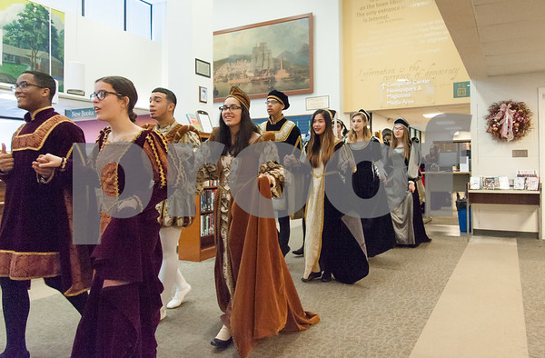 12/12/17 Wesley Bunnell | Staff The New Britain High School Madrigal Singers performed as they walked through the public library on Tuesday morning. The singers walk past the circulation desk on the main floor.