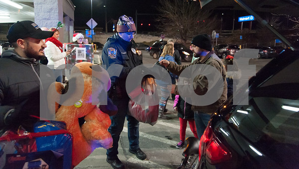 12/18/17 Wesley Bunnell | Staff The Bristol Police Explorers held a stuff the cruiser toy and clothing drive on Monday night outside of Walmart in Bristol. Ofc. Deluca, L, holds a donations including a large stuffed animal as he stands next to head Police Explorer Advisor Ofc. George Franek, middle as they continue to stuff the cruiser full of donations.