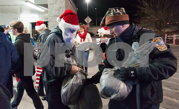 12/18/17 Wesley Bunnell | Staff The Bristol Police Explorers held a stuff the cruiser toy and clothing drive on Monday night outside of Walmart in Bristol. Police Explorer John Duncan, L, with a Santa hat and beard hands off donations to head Police Explorer Advisor Ofc. George Franek.
