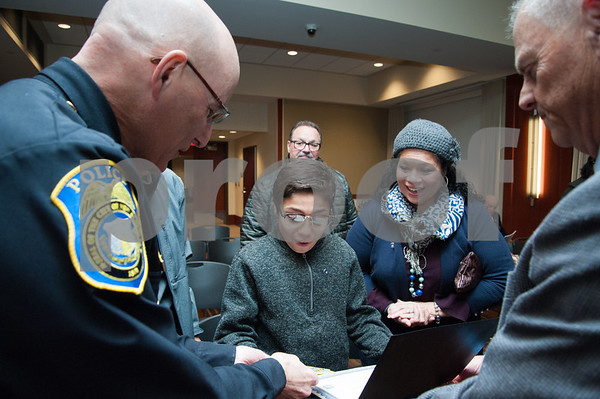 12/19/17 Wesley Bunnell | Staff 12 year old Armani Dante Rivera received recognition before the Police Commissioners meeting on Tuesday evening for his assistance to the New Britain Police Department. Armani Dante Rivera reacts after receiving an official New Britain Police patch from Chief James Wardwell, L, and commissioner chairman Howard Dyson, R, as his mother Victoria Rivera looks on.