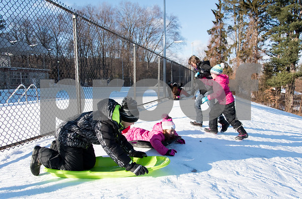 12/26/17 Wesley Bunnell | Staff Families took advantage of good sledding conditions at Page Park on Tuesday afternoon. Jedric Setula, age 12, and sister Corinne, age 9, prepare to race downhill as sister Kyleigh, age 10, gets some help from their mother Alida Roberts making it back up the slick hill.
