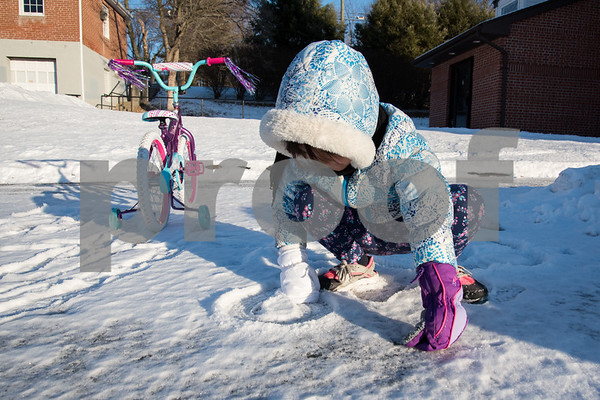 12/26/17 Wesley Bunnell | Staff Yizu Yezuilyny, age 5, draws hearts in the snow on Tuesday afternoon as she takes a break from riding her new bike she received for Christmas.