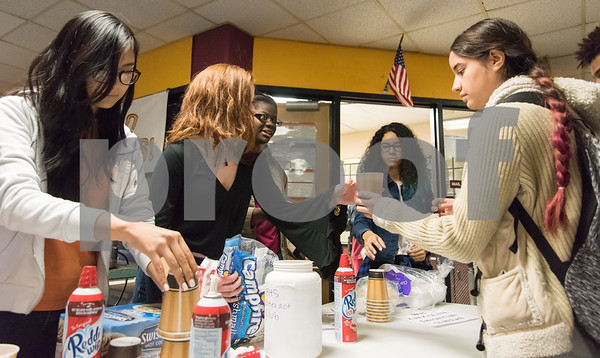 12/06/17 Wesley Bunnell | Staff Claire Palin hands a cup of hot chocolate to fellow student Kiaraliz Colon, R, as part of the New Britain High School Interact Club's fundraising efforts to benefit Warm the Children on Wednesday October 29th. Fellow club members Joann Khambaylarsirkul, L, Savannah Newton and Abigail Rivera are shown.