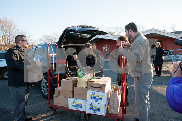 12/06/17 Wesley Bunnell | Staff Mayor Erin Stewart met with the owners of Alvarium Beer to deliver over 500 pounds of food to HRA food bank on Thursday afternoon. Mayor Stewart unloads food onto a car as HRA's Marlo Greponne looks on.