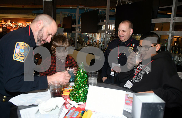 12/7/2017 Mike Orazzi | Staff Bristol Police officers Pete Sassu and Rich Guerrera with Alex McGrath and Jason Vanbeveren during a meet and greet held at Crystal Bees in Southington before shopping for Shop with a Cop, a one on one shopping experience pairing underprivileged children with law enforcement.