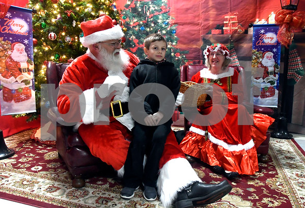 12/8/2017 Mike Orazzi | Staff Seven-year-old Noah Olson meets with Santa and Mrs Claus during the annual tree lighting held at the Plainville Fire Department Friday evening.