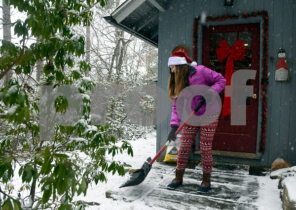 12/10/2017 Mike Orazzi | Staff Haley Guarriello shovels snow from the sidewalk at the Pebble House during the Annual Santas Farm Workshop held at Indian Rock Nature Preserve in Bristol Saturday morning.