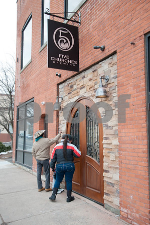 02/02/18 Wesley Bunnell | Staff Pedestrians peek through the windows of Five Churches Brewery located at 193 Arch St. on Thursday afternoon after a new sign and door were installed in preparation of its grand opening.