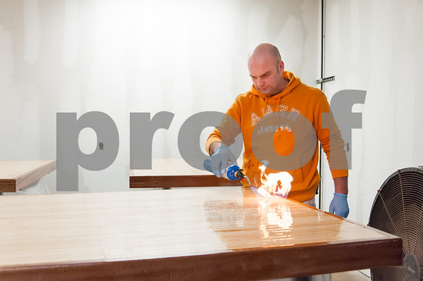 02/09/18 Wesley Bunnell | Staff Work continues on Friday afternoon at Five Churches Brewing at 193 Arch St in New Britain in anticipation of its grand opening that is yet to be determined. Marcin Giera of New Cambridge Painting uses a torch to help eliminate bubbles in the epoxy finish for the table tops which are made from reclaimed bowling alley lanes.