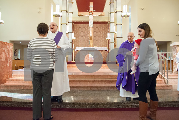 02/14/18 Wesley Bunnell | Staff Parishioners of St. Ann Church in Bristol line up to receive ashes on Ash Wednesday from Deacon Roger Albert, L, and Father Robert Russo.