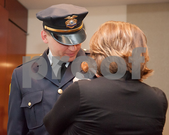 02/15/18 Wesley Bunnell | StaffThe New Britain Police Department promoted three of its own including the first female captain in its history. Adam Rembisz who was promoted to lieutenant has his badge pinned on his uniform by his mother.