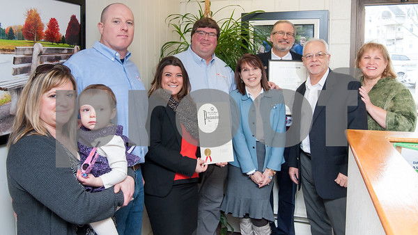 02/20/18 Wesley Bunnell | Staff Collier Electric Corp celebrated 25 years in business with presentations on Tuesday morning by Mayor Erin Stewart and Representative William Petit Jr. Marlo Lagosz, L, holds daughter Addalyn while standing next to finance Bryson Burse who is Vice President and Secretary, Mayor Erin Stewart, President Scott Pehmoeller, Administrative Assistant and Safety Officer Stacey Rich, Representative William Petit Jr., Economic Development Director Bill Carroll and Treasurer Donna Pehmoeller.