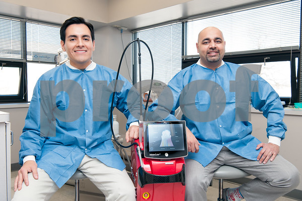 02/20/18 Wesley Bunnell | Staff Edgar Salas D.M.D. , L, and Rajesh Gohel D.M.D. of OM Dental sit next to their new Waterlase iPlus machine which is a better and less invasive treatment for gum disease.