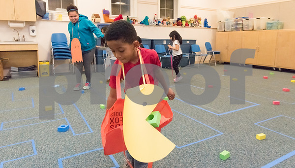 02/26/18 Wesley Bunnell | Staff Div'enchii, age 7, picks up the dots as the title character Pac-Man in the 1980's video game in a life size version at the Bristol Public Library on Monday night. Stalking him as a ghost is Jabreea, age 7.