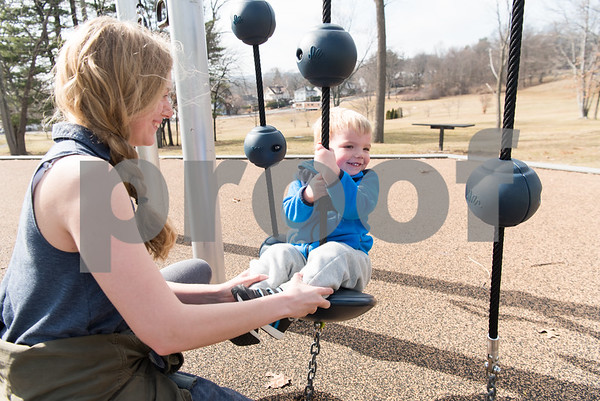 02/21/18 Wesley Bunnell | Staff Teacher Melissa Bengston helps Rowen, age 2, as he sits on the wobblers at the Walnut Hill Park on a warm Wednesday morning. The two are from the New Britain YMCA Childcare Academy at 111 Hart St.