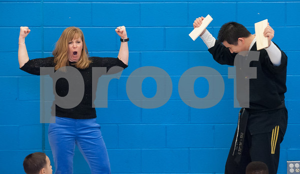02/22/18 Wesley Bunnell | Staff Master Hyung Yang from Yang's U.S. Taekwondo Academy in Newington gave demonstrations on Thursday 2/22 at Lincoln School which involved teachers and elementary students. Teacher Amy Greaves raises her fists after breaking a wood board held by Master Yang.