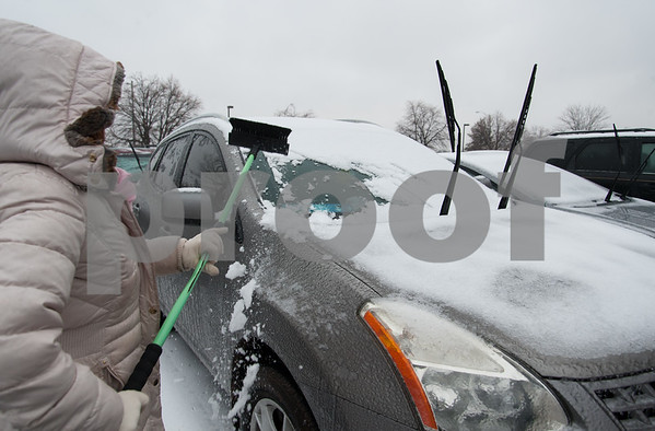02/07/18 Wesley Bunnell   Staff Mayra Disdiel cleans her car off Wednesday afternoon in downtown New Britain as the snow started to give way to rain and ice.