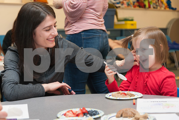 01/24/18 Wesley Bunnell | Staff Registered Dietitian Katie Shepherd brought her Food Explorers program to the Bristol Public Library on Wednesday morning to work with a group of pre school age children. The program teaches healthy food choices through sensory experiences and activities followed with hands on food exploration. Bukuroshe Belieri, L, sits with daughter Emma, age 3, as she enjoys her plate of food towards the end of the program.