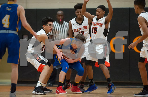 01/26/18 Wesley Bunnell   Staff E.C. Goodwin boys basketball vs Ellis Tech on Friday evening at E.C. Goodwin High School. Tying up the Ellis Tech player are Sam Lopez (21), Jesse Tandoh (12) and Joshleen Peeples (15).