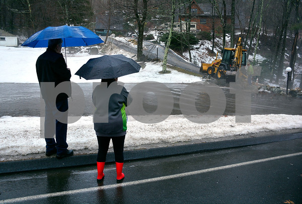 1/12/2018 Mike Orazzi | Staff Plymouth residents Rich Blair and Sherry Kizzia watch as a crew from public works opens a drain causing a flooding issue on Old Waterbury Road during Friday's rain storm.