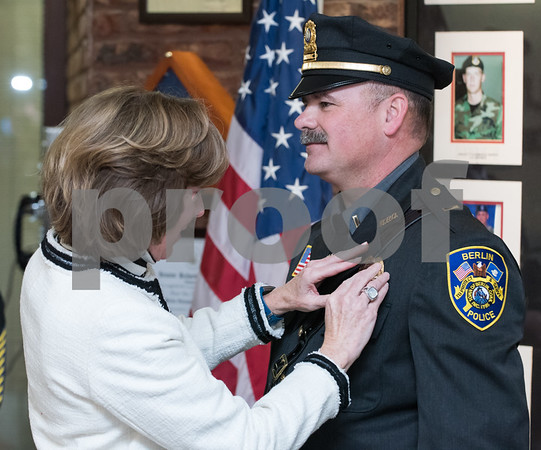 01/17/18 Wesley Bunnell | Staff The Berlin Police Department held a promotion ceremony for two officers on Wednesday evening at town hall. Eileen Gallupe pins the badge on her husband Lieutenant Drew Gallupe.