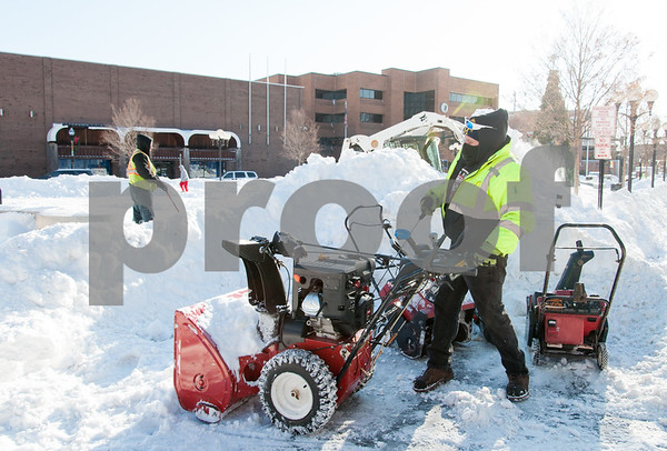 01/05/18 Wesley Bunnell | Staff City workers cleared out Central Park on Friday morning following Thursday's blizzard. Dan Cummings starts up a snowblower to help clear the sidewalks around the park.