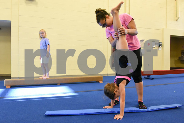 070517 Wesley Bunnell | Staff Hailie Tedeschi, age 7, receives instruction from Chantel Blake as Keira James, age 6, looks on during gymnastics class on Wednesday afternoon at the YWCA in New Britain.