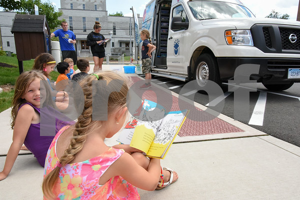 070517 Wesley Bunnell | Staff Lyla Bray, age 5, looks over as Rylee Keeley, age 6, reads One Fish, Two Fish, Three Fish, Blue Fish by Dr. Seuss outside of the Bristol Boys and Girls Club. The books are from the Bristol Board of Education Book Mobile which made a visit to the club.