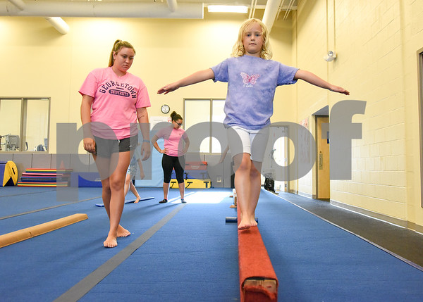 070517 Wesley Bunnell | Staff Keira James practice on the balance beam with the help from instructor Emily Bonomi during gymnastics class on Wednesday afternoon at the YWCA in New Britain.