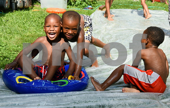 071717 Wesley Bunnell | Staff Zayvion Robinson, age 2, slides on a tube down a home made slip n slide with help from Shamar Lebby, age 5, as Kainan Cummings, age 4, sits off to the right.