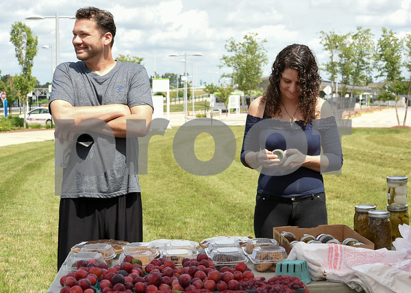 071717 Wesley Bunnell | Staff Monday afternoon marked the first farmers' market of the year at the New Britain Fastrak location with a stand from Dondero Orchards. Michael and Amanda Palmisano looks over the selection.