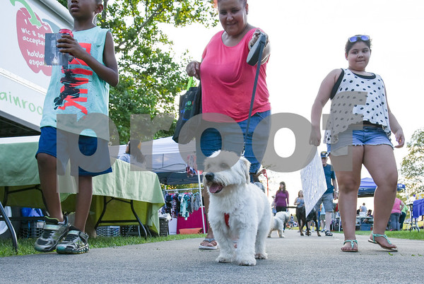 071917 Wesley Bunnell | Staff The second annual Pets-A-Palooza was held at Walnut Hill Park on on Wednesday evening. Maria Mirabel and family walk their dog Nike past the vendor booths.