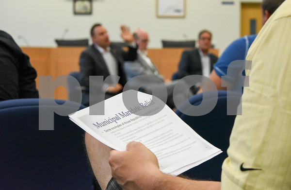 071917 Wesley Bunnell | Staff A handout dealing with the current budget is held by an audience member as Representative Rob Sampson, State Senator Joe Markley and Representative John Fusco hold their post session town hall meeting on Wednesday, July 19 at the Southington Municipal Center.