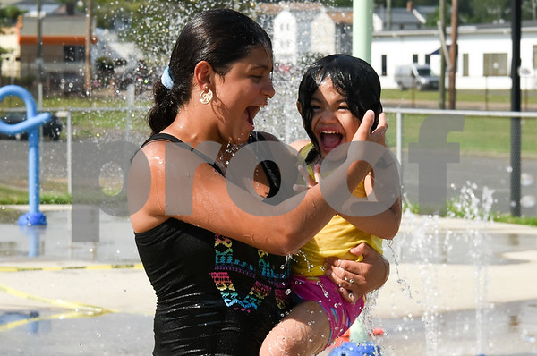 072017 Wesley Bunnell | Staff Both Abneliz Alamo, age 13, and Liushka Arroyo, age 2 are all laughs as they cool down at the Chesley Park Splash Pad on Thursday afternoon.