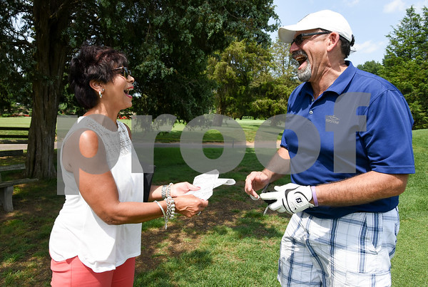 072117 Wesley Bunnell | Staff The Boys and Girls Club of New Britain held the 13th Annual Chuck Roby Golf Tournament, sponsored by Farmington Bank, on Friday at Stanley Golf Course. Lynn Roby Knapp, L, enjoys a laugh with tournament participant Ron Albert as he buys 50/50 raffle tickets.