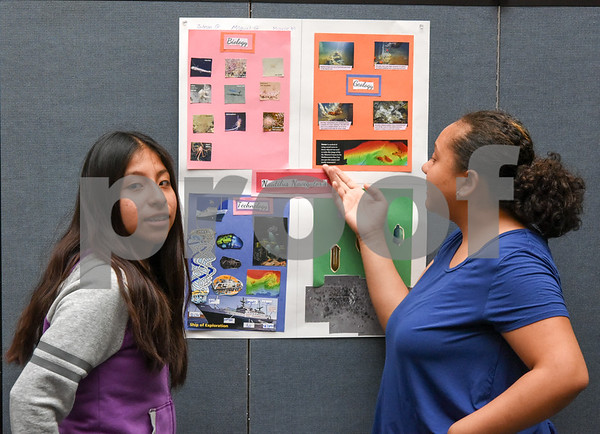 072117 Wesley Bunnell | Staff Middle and High School students completed a two week CCSU TRiO program with presentations and awards on Friday afternoon. Michelle Montero, L, and partner Julyssa Garcia look over their project on deep sea exploration.