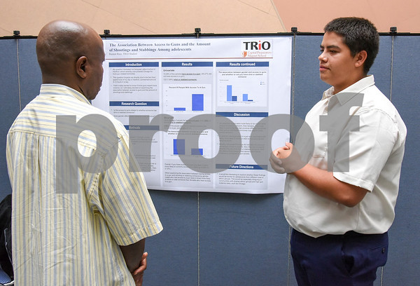 072117 Wesley Bunnell | Staff Middle and High School students completed a two week CCSU TRiO program with presentations and awards on Friday afternoon. Ramon Ruiz, R, discusses his research project on access to guns and shootings.