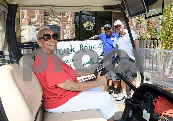 072117 Wesley Bunnell | Staff The Boys and Girls Club of New Britain held the 13th Annual Chuck Roby Golf Tournament, sponsored by Farmington Bank, on Friday at Stanley Golf Course. Chuck Roby's wife Helen Roby sits in a golf cart with Christopher Roby and Chuck Roby Jr. in the background.
