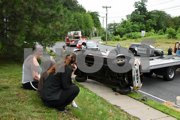 072417 Wesley Bunnell | Staff Emergency crews responded to a pick up truck rollover on Mountain Rd in Bristol on Monday afternoon. The driver, L, sits with family as they watch the truck pushed back onto its tires by the tow truck.