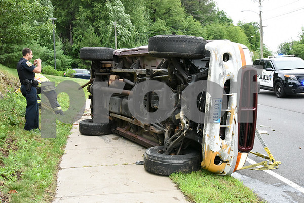 072417 Wesley Bunnell | Staff Emergency crews responded to a pick up truck rollover on Mountain Rd in Bristol on Monday afternoon. A police officer takes photos of the truck.