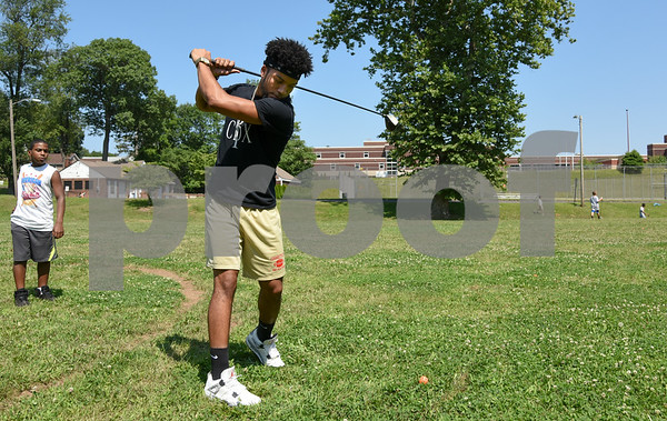 073117 Wesley Bunnell | Staff Volunteer and recent New Britain High graduate Donovan Dorce practices his golf swing on Monday afternoon during the Extreme Summer Program. The program is through the New Britain Board of Education.
