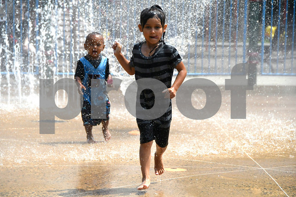 7/11/2017 Mike Orazzi | Staff Malka and Araynna Beland while cooling off in the Rockwell Park spray park Tuesday afternoon.