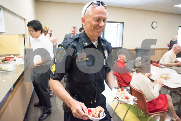 071217 Wesley Bunnell | Staff New Britain TRIAD served up ice cream at the New Britain Senior Center on Wednesday afternoon. New Britain Police Sgt. Art Powers walks two sundaes to a table.