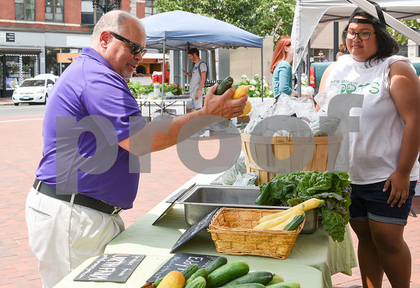 071217 Wesley Bunnell | Staff The first farmers market of the year in Central Park took place on Wednesday featuring local businesses and pizza truck. Executive Director at New Britain Downtown District's Gerry Amodio chooses vegetables grown by Urth Farms from the New Britain Roots truck.