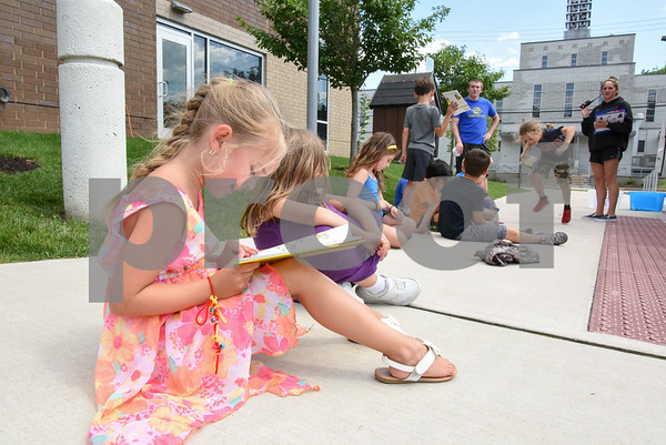 070517 Wesley Bunnell | Staff Rylee Keeley, age 6, reads One Fish, Two Fish, Three Fish, Blue Fish by Dr. Seuss outside of the Bristol Boys and Girls Club. The books are from the Bristol Board of Education Book Mobile which made a visit to the club.