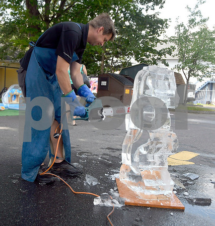7/13/2017 Mike Orazzi | Staff Bill Covitz carves a seahorse out of a block of ice with a chainsaw during a water carnival held at the Imagine Nation Museum and Early Learning Center in Bristol Thursday morning.